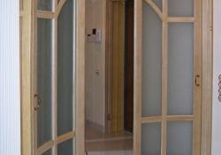 радиусная стеклянная раздвижная дверь - отделка массивом и шпоном